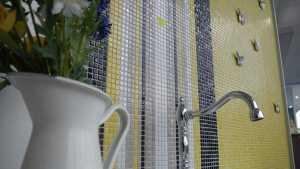 Eine mit Mosaiken verkleidete Wand im Badezimmer.