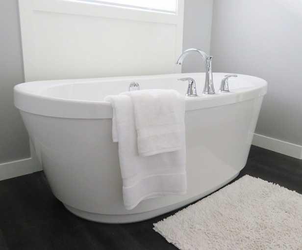 Schwarze Badfliesen und weiße Badewanne